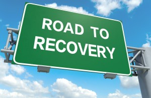 A road sign with road to recovery words on sky background