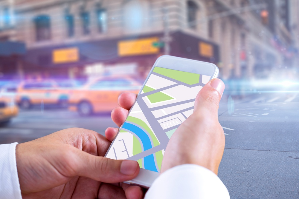 Man using map app on phone against blurred new york street