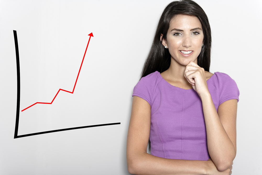 Professional working woman in corporate purple dress, with a concept graph displaying an increase.